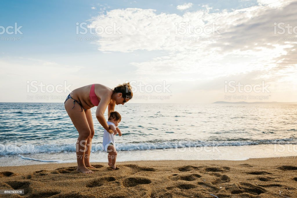 Babymädchen unterstützt von ihrer Mutter, die versucht, zu Fuß Lizenzfreies stock-foto