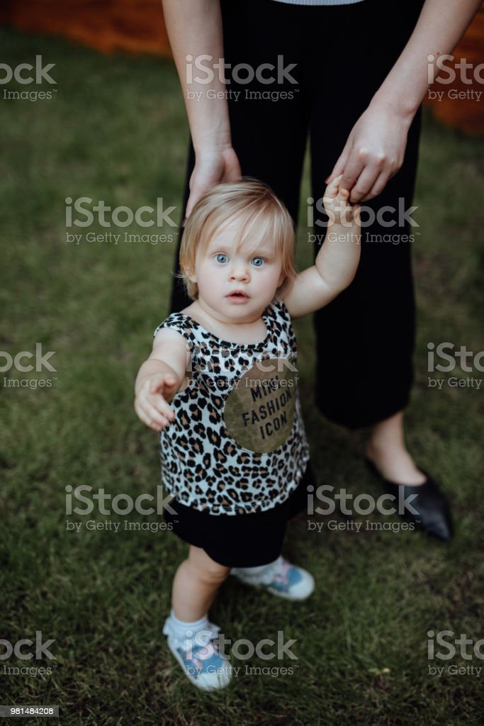 Baby girl taking her first steps with help of her aunty stock photo