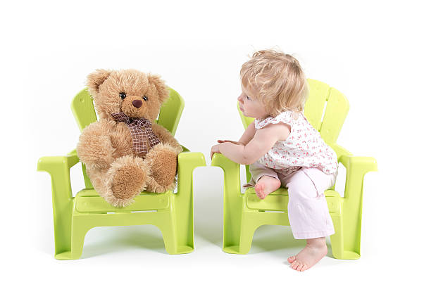 Baby Girl Talks with Her Toy Bear stock photo