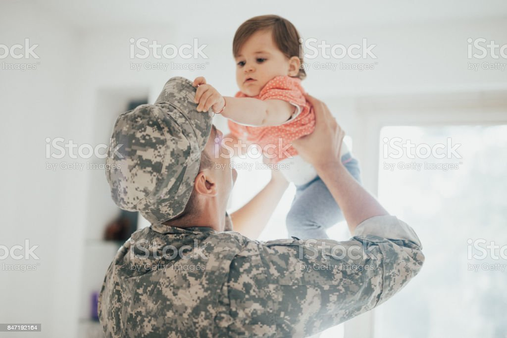 Baby girl trying to take off dad's military hat - Royalty-free Adult Stock Photo