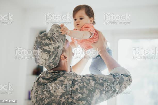 Baby Girl Trying To Take Off Dads Military Hat Stock Photo - Download Image Now