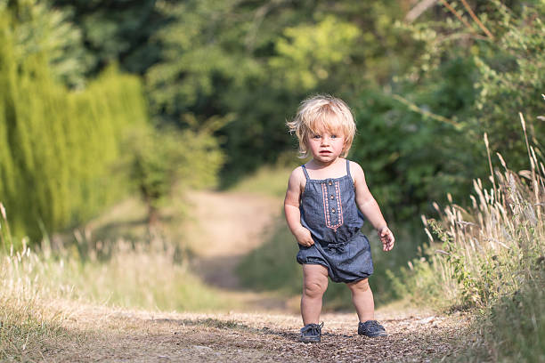 Baby girl walks on green forest path stock photo