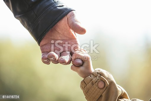 istock Baby girl warm jacket and cap c grandfather hands 614416724