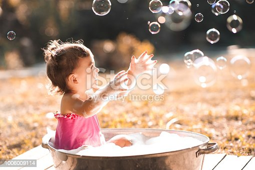 Laughing baby girl 1 year old playing with soap bubbles outdoors.
