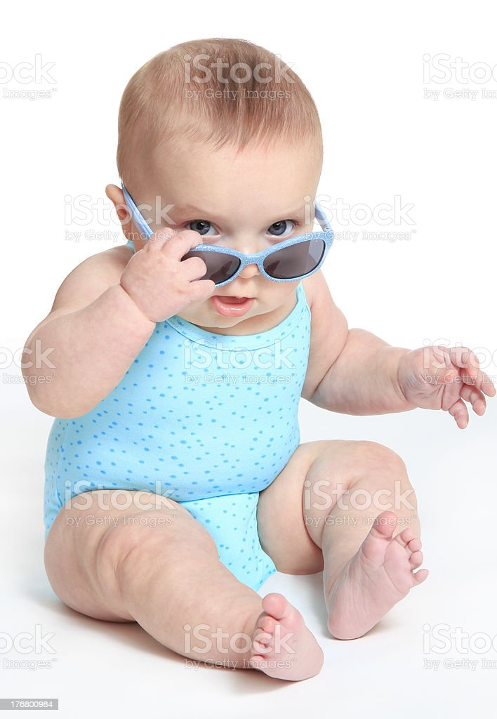 Baby girl wearing a blue swimsuit and sunglasses stock photo