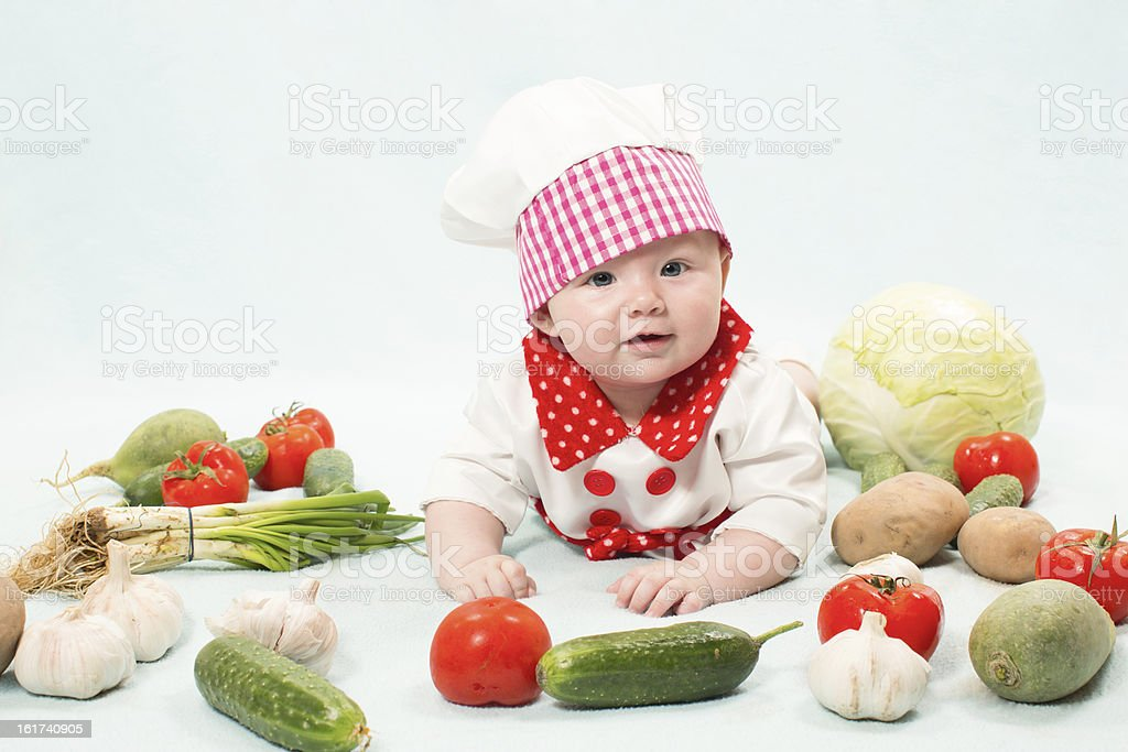 Baby girl  wearing a chef hat with vegetables. royalty-free stock photo