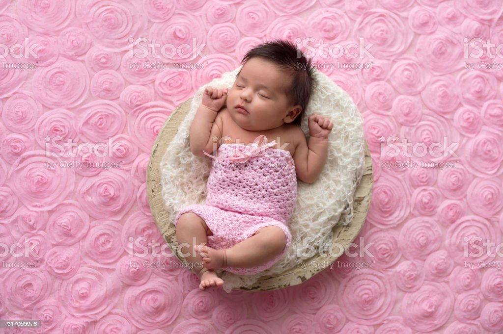 Baby Girl Wearing a Pink, Crocheted Romper Portrait of a sleeping, one month old baby girl wearing a crocheted, pink romper. 0-1 Months Stock Photo