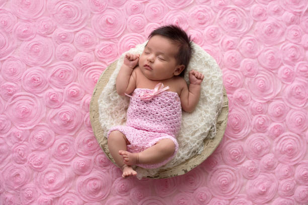 Baby Girl Wearing a Pink, Crocheted Romper Portrait of a sleeping, one month old baby girl wearing a crocheted, pink romper. baby girls stock pictures, royalty-free photos & images