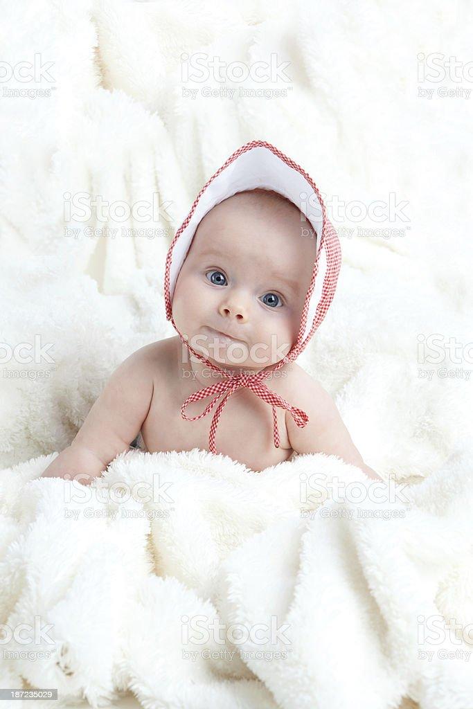 Baby Girl Wearing Hat Sitting in White Blanket stok fotoğrafı