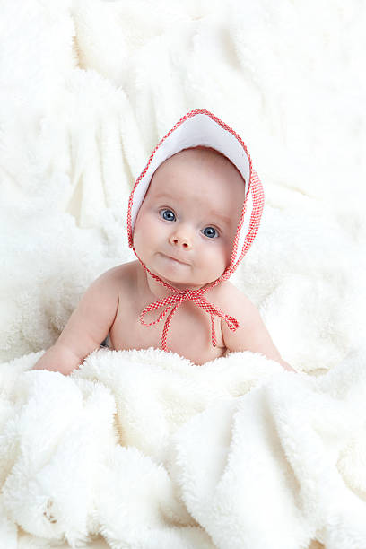 Baby Girl Wearing Hat Sitting in White Blanket Baby girl wearing red and white bonnet sitting on white blanket, looking at camera. bonnet stock pictures, royalty-free photos & images