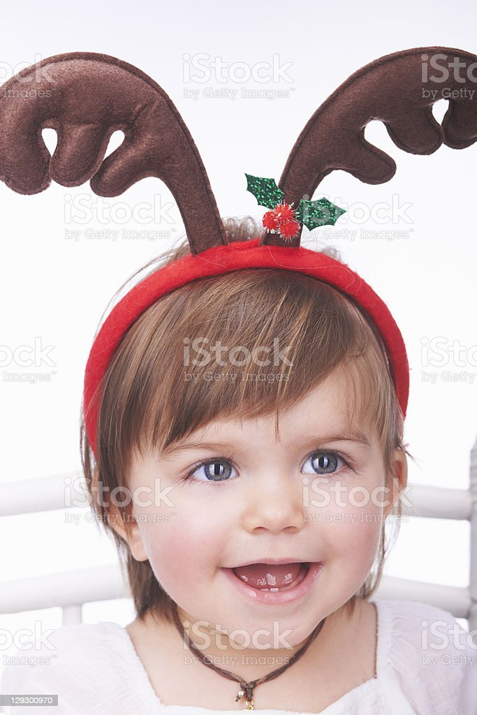 Baby girl wearing reindeer antlers stock photo