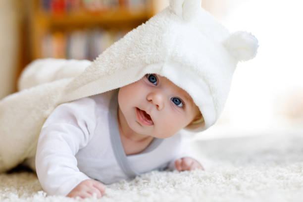Baby girl wearing white towel or winter overal in white sunny bedroom stock photo