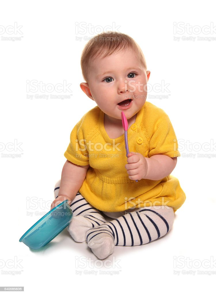 Baby girl with a bowl and spoon stock photo