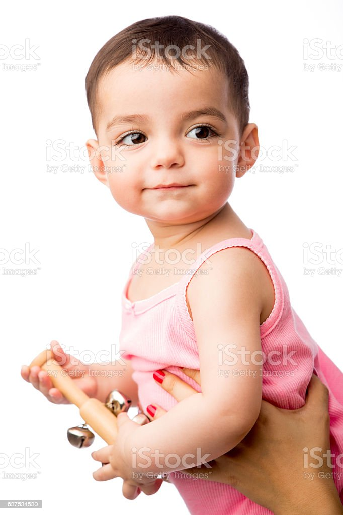 Baby girl with a toy musical rattle and smiling - foto de stock