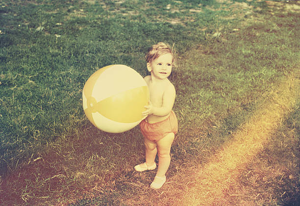 baby girl with beach ball - 1970s style stock photos and pictures