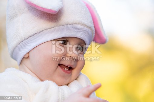 155096501 istock photo Baby girl with chubby cheeks in bunny costume smiling 1093114826