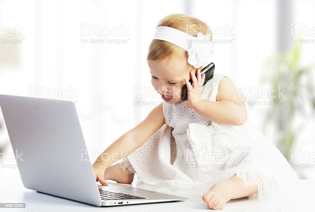 baby girl with computer laptop,  mobile phone stock photo