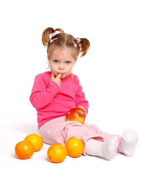 baby girl with fruits - pigtails stock photos and pictures