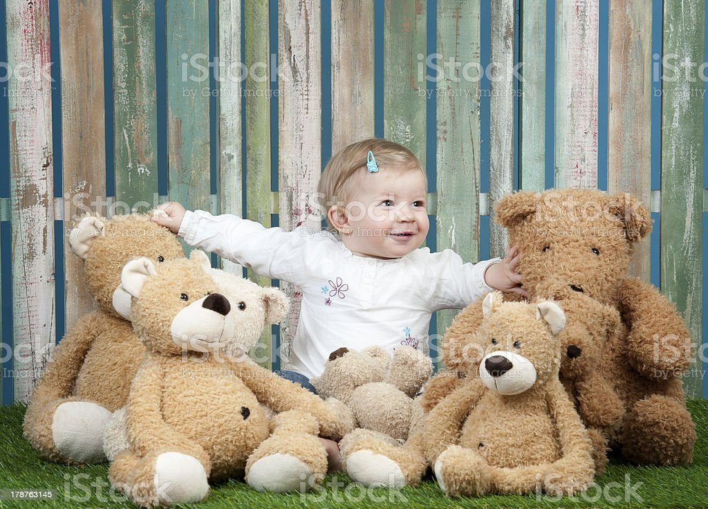 baby girl with group of teddy bears, seated on grass stock photo