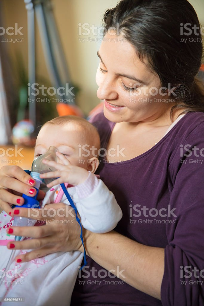 Baby girl with inhalator stock photo