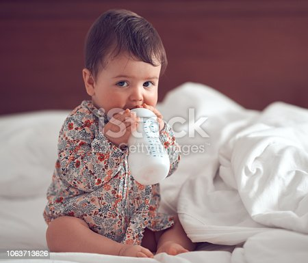 cute baby girl holding milk bottle and looking at camera.
