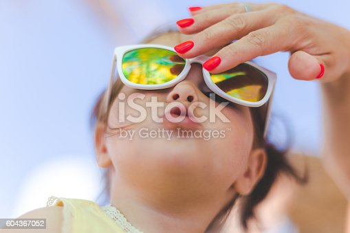 istock baby girl with sunglasses on a beach 604367052