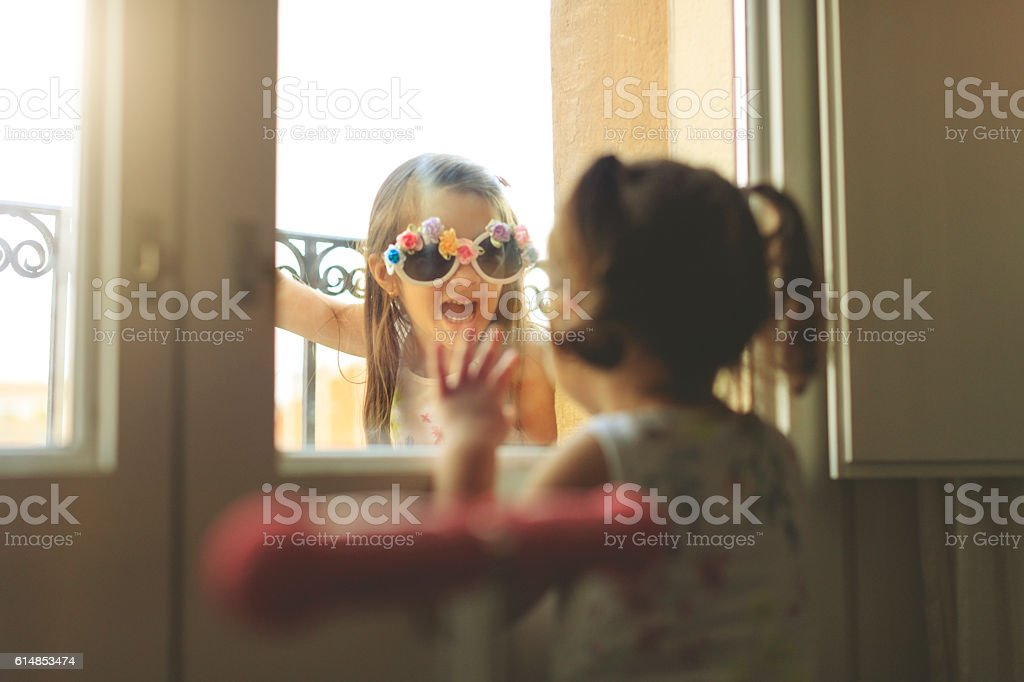 Baby girls together by a window stock photo