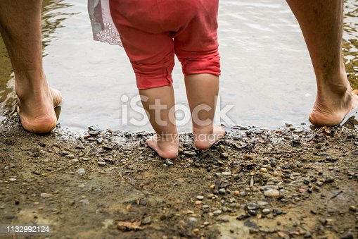 Father helping his daughter taking her first steps in a fishing lake of Quebec.