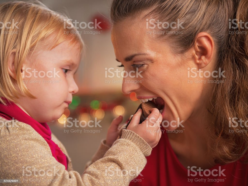 baby giving mother bite of chocolate santa stock photo