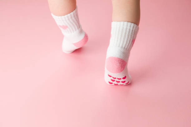 Baby going on light pink floor background. Pastel color. Feet in anti slip socks. Infant first steps. Closeup. Back view. stock photo