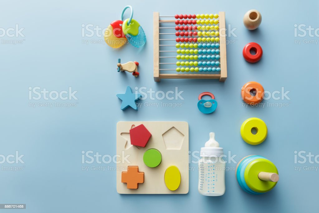 Baby Goods: Wooden Toy, Milk Bottle, Pacifier and Teething Ring Still Life stock photo