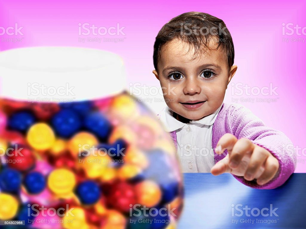 baby grubbing candies in candy shop stock photo