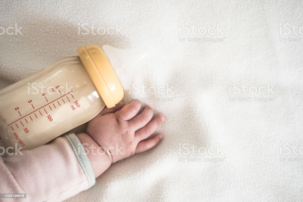 Baby hand and Bottle of Mother breast milk on white blanket background for text space stock photo