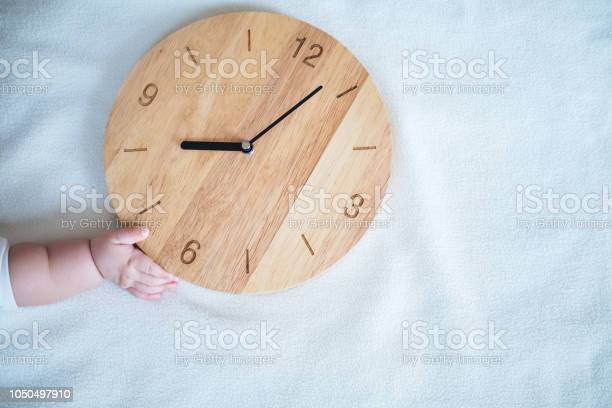 Baby hand and wooden clock on blanket background picture id1050497910?b=1&k=6&m=1050497910&s=612x612&h=gornaelwazvgfaxpd0q9itna5tfmgex5xrqqm 3iiaw=