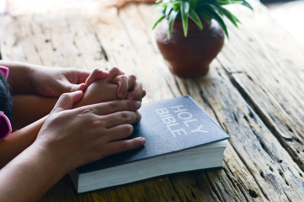 Baby hand holding in mother hands for  prayer. stock photo