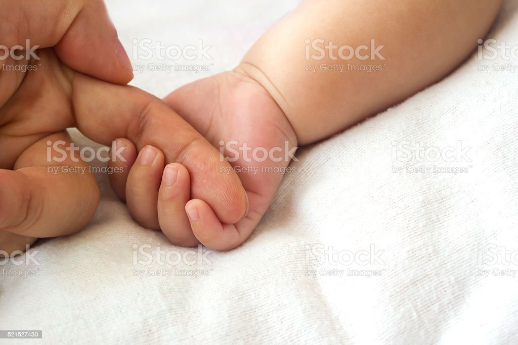 Baby hand holding mother finger. stock photo
