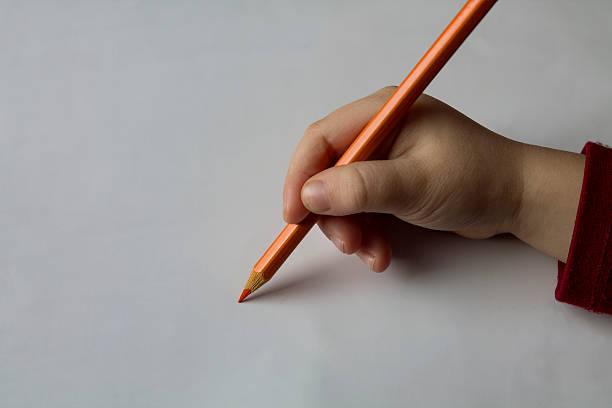 Baby Hand Holding Orange Pencil stock photo