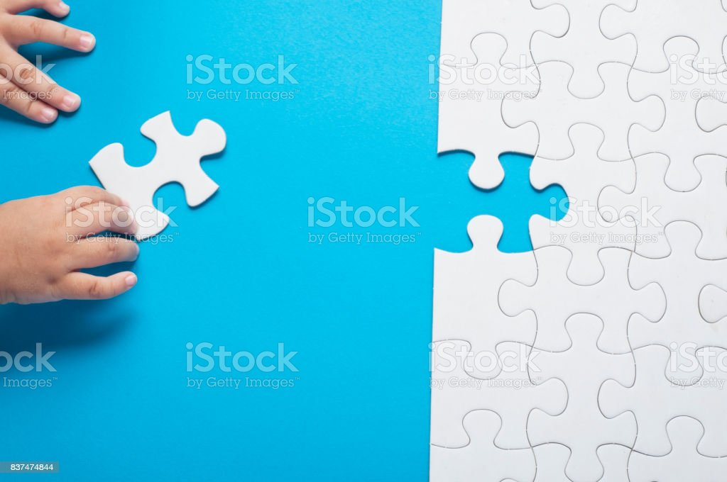 Baby hand holding piece of white puzzle on blue background. Business and team work concept. stock photo