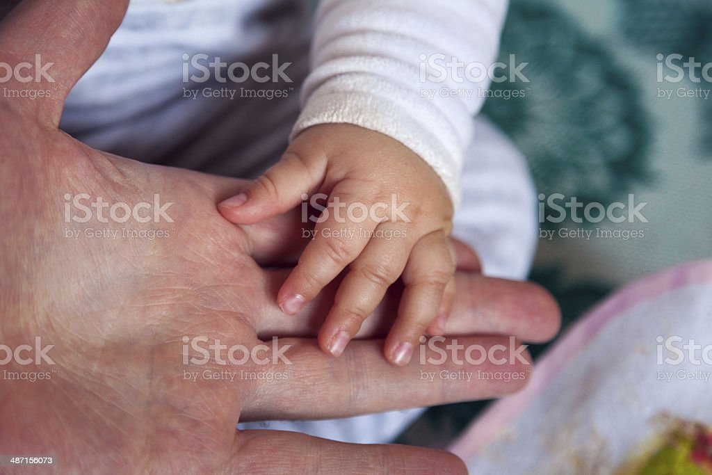 Baby hand on adult hand stock photo