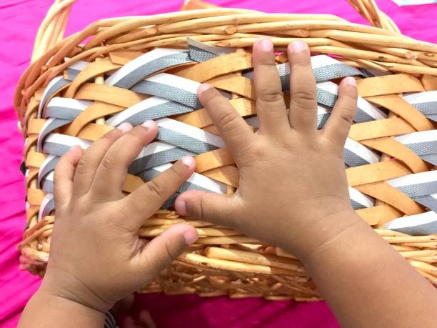 Baby hand on weaved basket stock photo