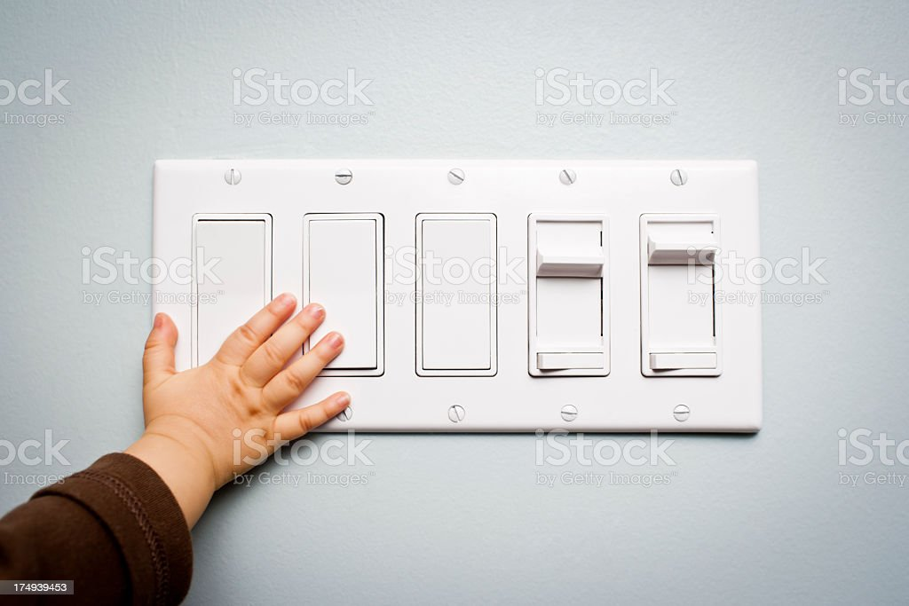 Baby hand touching a panel with five light switches stock photo
