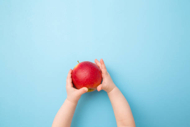 Baby hands holding red apple. Fresh fruit. Empty place for text on light blue table background. Pastel color. Closeup. Point of view shot. Top down view. stock photo