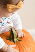 6-month-old baby girl holding a big orange Pumpkins on a wooden floor in bright natural light.