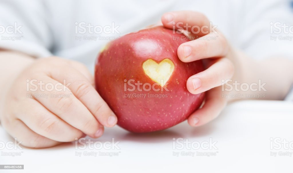 Baby hands with apple isolated on white stock photo