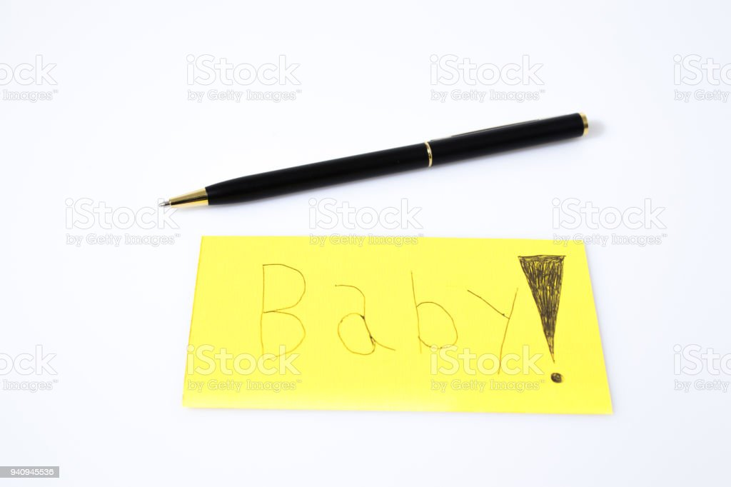 Baby handwrite with a pen on a yellow paper composition stock photo