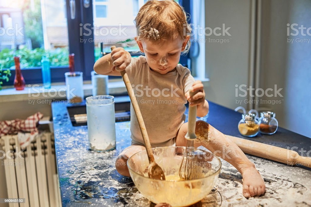 baby having fun making a mess in the kitchen stock photo