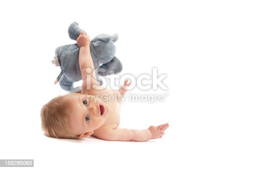Blue eyed blond hair nine month old cute baby boy isolated on white having fun with his stuffed elephant.