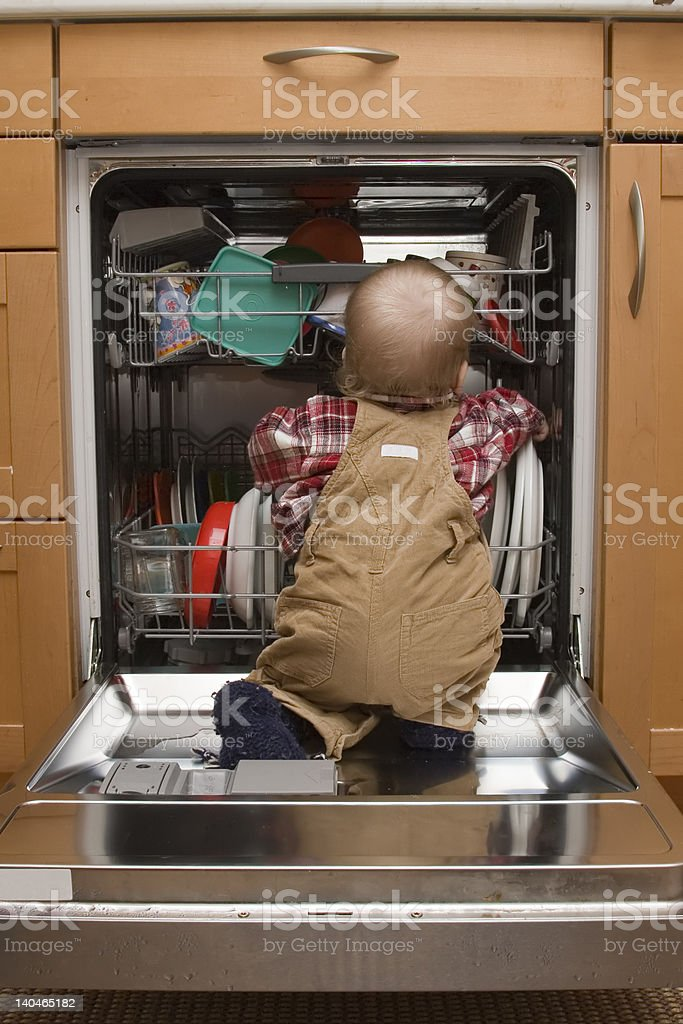 baby 'helping' in the kitchen stock photo