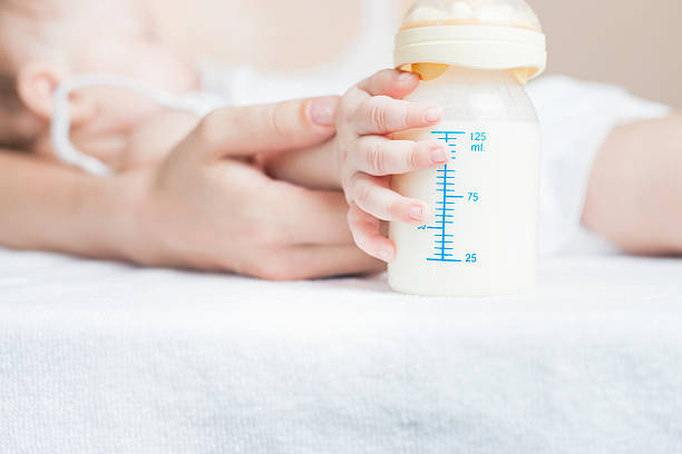 baby holding a baby bottle with breast milk - formula 1 個照片及圖片檔