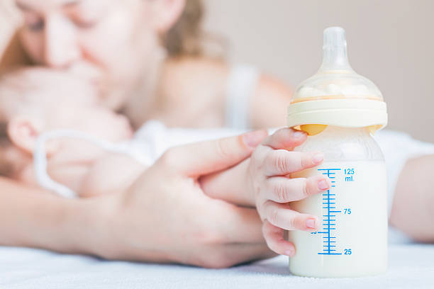 Bebé sosteniendo una botella de bebé con leche materna - foto de stock
